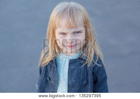 little girl looking at the camera and scowling