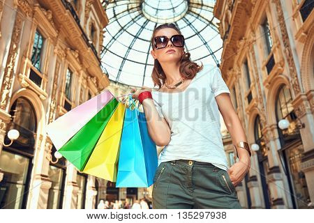 Discover most unexpected trends in Milan. Fashion woman in eyeglasses with colorful shopping bags in Galleria Vittorio Emanuele II looking into the distance