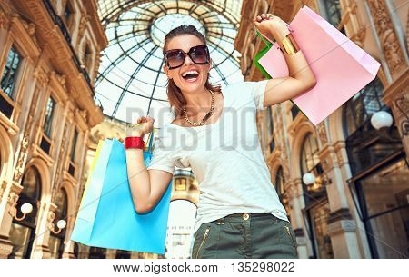Discover most unexpected trends in Milan. Portrait of smiling fashion woman in eyeglasses with colorful shopping bags in Galleria Vittorio Emanuele II rejoicing