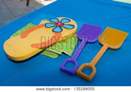 Flip flop sandal and sand shovels as decorations.