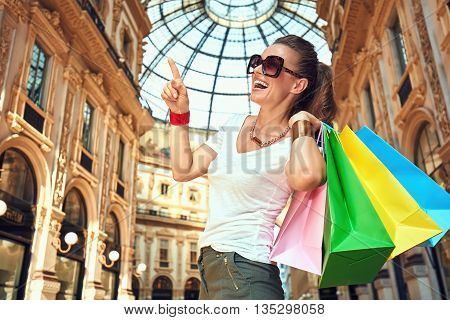 Discover most unexpected trends in Milan. Portrait of happy fashion woman in eyeglasses with colorful shopping bags in Galleria Vittorio Emanuele II pointing on something