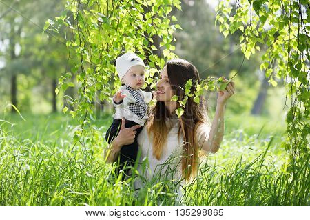 Happy woman and child in the blooming spring garden.Mother with child under a birch. Mothers day holiday concept