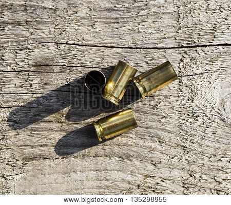 Stacked empty bullet shells placed on a wooden table.