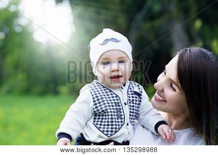 Happy woman and child in the blooming spring garden.Happy child, happy mom. Mothers day holiday concept