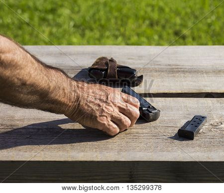 Old person is touching a metal gun.