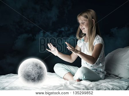 Cute girl sitting in bed and looking at moon planet
