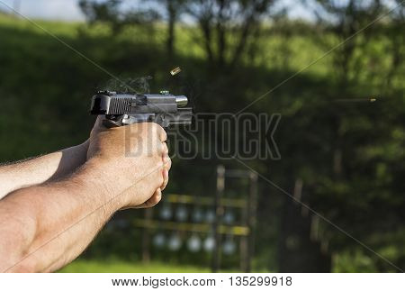 Person is holding a gun and it's aiming at something.