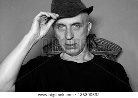 Man with a serious gaze and wearing elegant hat and t-shirt posing in studio in black and white