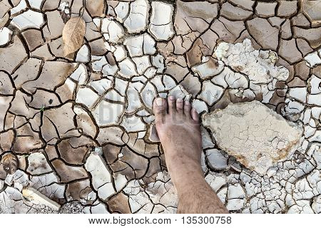 Barefoot Standing On Dry And Cracked Ground, Conservation Concept, Dramatic Style
