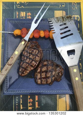 Grilled steaks and tomatoes froma summer BBQ along with cooking utensils on a serving tray