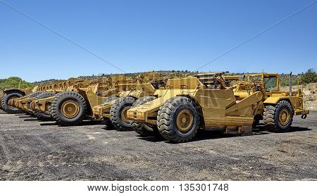 Heavy equipment wheeled motor scrapers for road building and construction