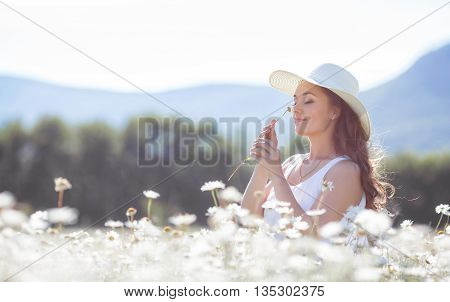 Portrait of beautiful young woman in a white hat with a wide brim,brunette with long curly hair, in a white summer dress,a beautiful smile,on a neck a gold chain,posing in a white field of blooming daisies in a mountain area