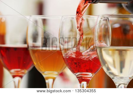 Red wine pouring into glasses, closeup