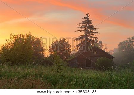 Abandoned wooden house in foggy at Solstice sunrise