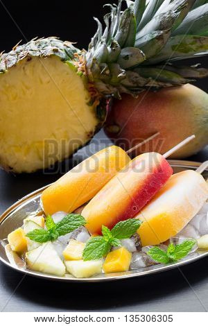 Pineapple mango strawberry sorbet ice cream on silver plate with ice cubes, fruit pieces near half of pineapple, mango on a black background. Pineapple mango strawberry sorbet ice cream popsicles.