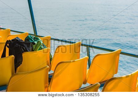 Black and mint bags on a plastic fiberglass chairs of ferry boat. Selective Focus.
