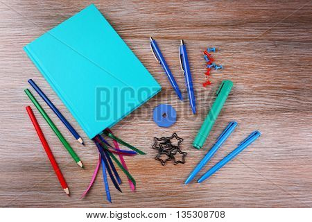 Notebook with stationery on wooden background
