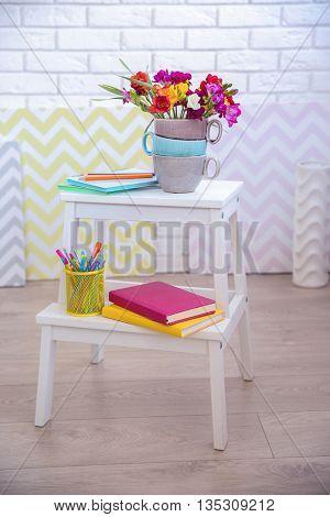 Beautiful freesia flowers on wooden stool on white brick wall background