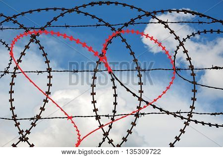 Natural heart shape (digitally coloured red) in a barbed wire on sky background. Love, freedom, peace and compassion concepts.