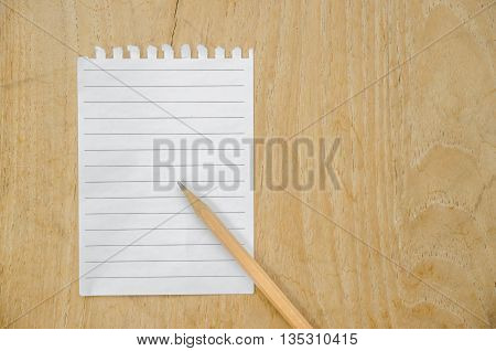 Notebook Paper And Used Pencil On Wood Background
