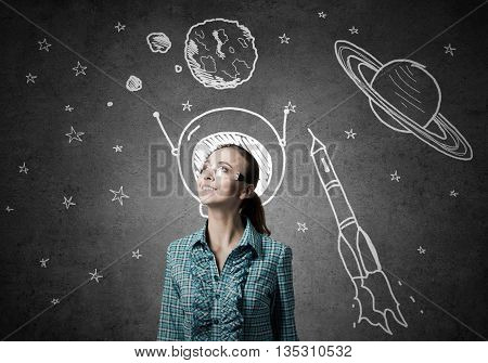 Student girl in jacket and glasses dreaming to become astronaut