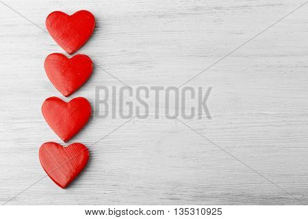 Wooden hearts on light background