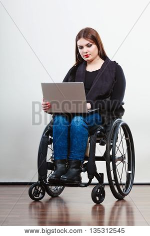 Technology and mobile equipment. Disabled handicapped girl with laptop computer. Young woman business worker on wheelchair.