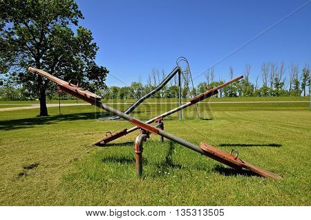 An old styled pair of teeter totters and an old metal slippery slide are located in a city park of a small rural town.