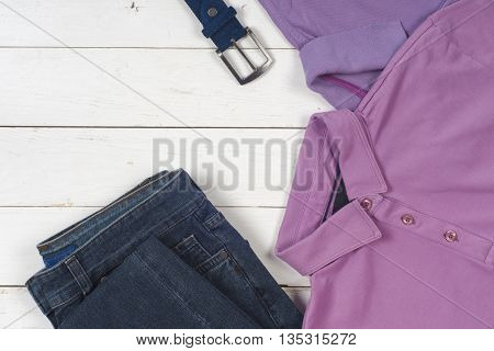 set of men's clothing and shoes on wooden background. Sports T-shirt and sneakers in bright colors. Top view