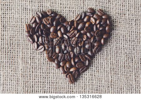 Burlap texture with coffee beans heart shape background. Sack cloth burlap texture, love coffee. Natural sackcloth canvas background with coffee heart and copy space. Coffee border at hessian textile
