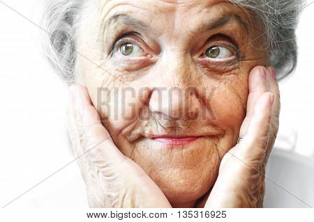 Portrait of older pretty woman with a few wrinkles. Touching her face with hands