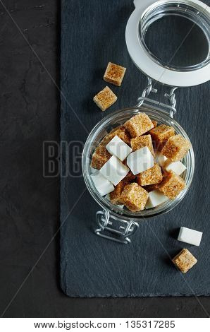 White And Brown Sugar Cubes In A Glass Jar