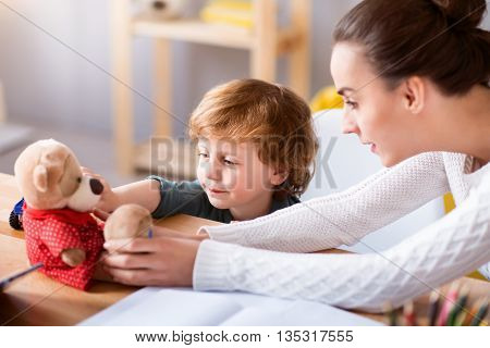 Look at your teddy. Concentrated woman and her child sitting at the table and looking at the teddy bear