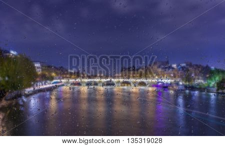 Abstract blurry background with water drops: view through the window Paris by night France