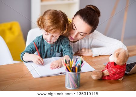 What is it. Young mother looking at her little boy drawing while sitting with him at the table