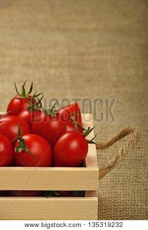Red Cherry Tomatoes In Wooden Box On Canvas