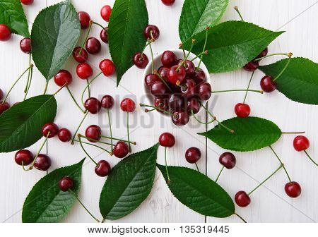 Sweet fresh cherries with green leaves background. Scattered cherries on white rustic wood. Cherry fruit and leaf backround. Organic cherries at wood table, top view. Food background.