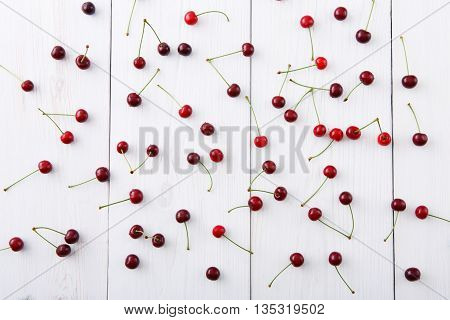 Sweet fresh cherries background. Scattered cherries on white rustic wood pattern. Cherry fruit backround. Garden fresh organic cherries at wooden table, top view. Food background.