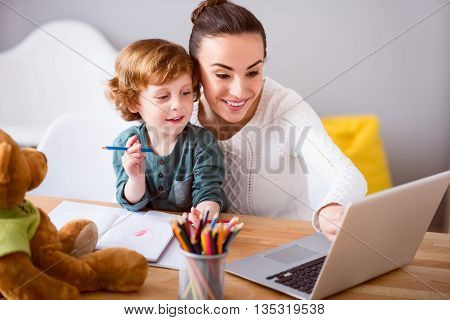 Hey look. Young happy mother sitting at the table with her son on her knees and they looking at the laptop