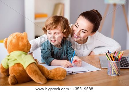 Idea for drawing. Smiling beautiful mother looking at the teddy bear while sitting at the table with her little son holding color pencils