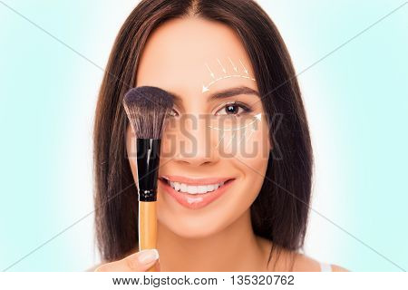 Close Up Portrait Of Pretty Woman Holding Makeup Brush Near Eye With Arrows