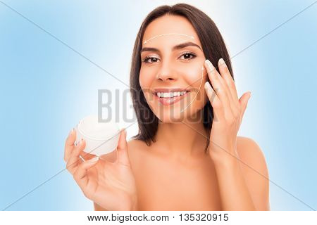 Portrait Of Attractive Young Woman Applying Cream On Her Face With Arrows Of Effect