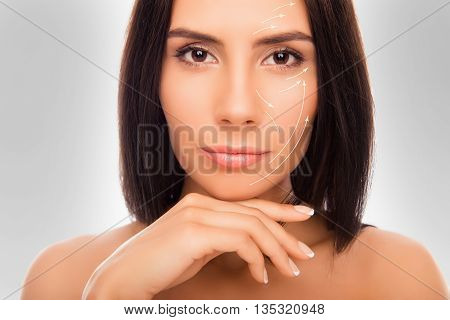 Close Up Portrait Of Calm Brunette Touching Her Skin