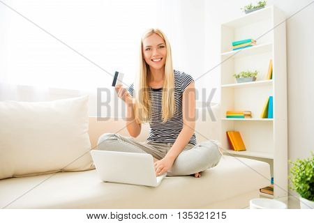 Happy Young Woman Showing Credit Card And Doing Internet Shopping