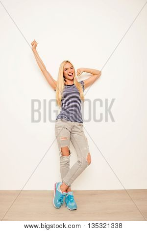 Stylish Pretty Girl In Ripped Jeans Yawning And Stretching