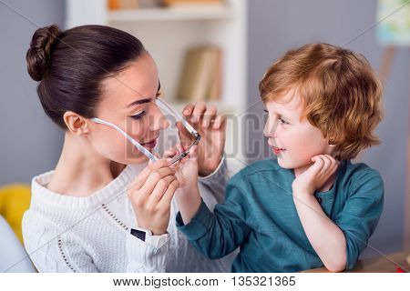 Give it to me. Pleasant young mother taking off her glasses while her son touching them