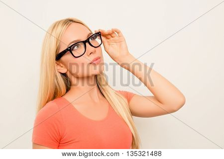 Portrait Of Young Atractive Woman Touching Her Glasses And Dreaming