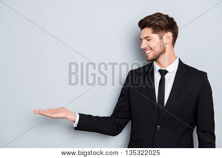 Cheerful Young Man In Black Suit Presenting Product