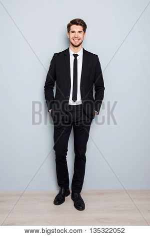Successful Smiling Businessman In Suit Holding Hands In Pockets