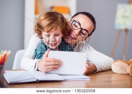 Raise interest. Young smiling mother with glasses and her son looking at a tablet while sitting at the table